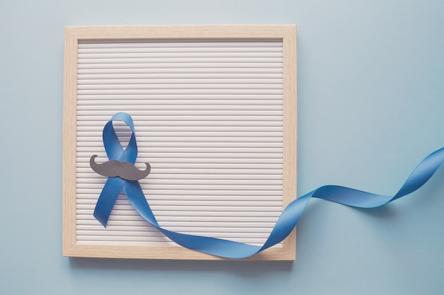 Blue ribbon with mustache on letter board, prostate cancer awareness, men health awareness