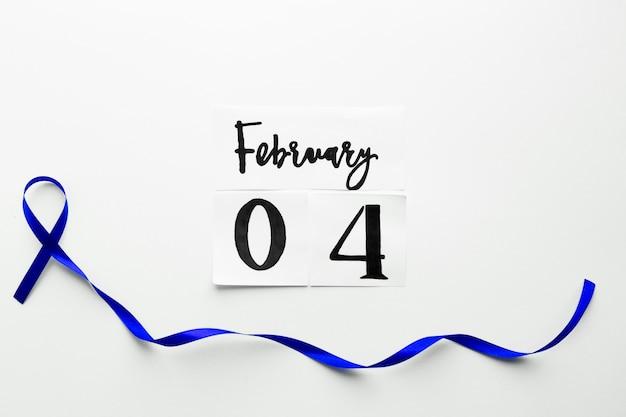 Nastro blu sotto la data del giorno del cancro mondiale