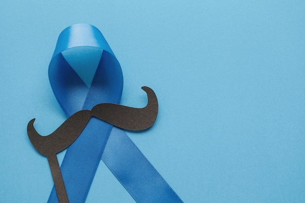 Blue ribbons with mustache on blue, prostate cancer awareness