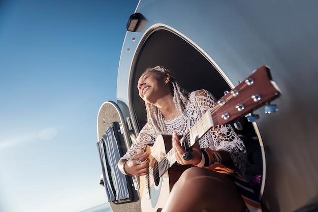 青いリング。ギターを弾く巨大な青いリングを身に着けている白いドレッドヘアを持つアフリカ系アメリカ人の女性