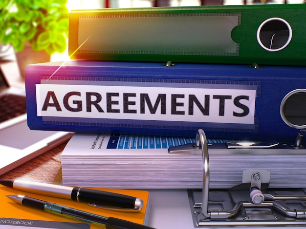 Blue ring binder with inscription agreements on background of working table with office supplies and laptop. agreements business concept on blurred background. 3d render.
