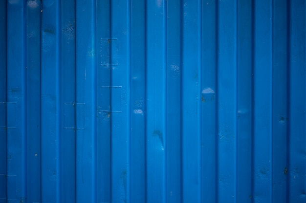 Blue ripple of container wall looks like waves on zinc roof texture.