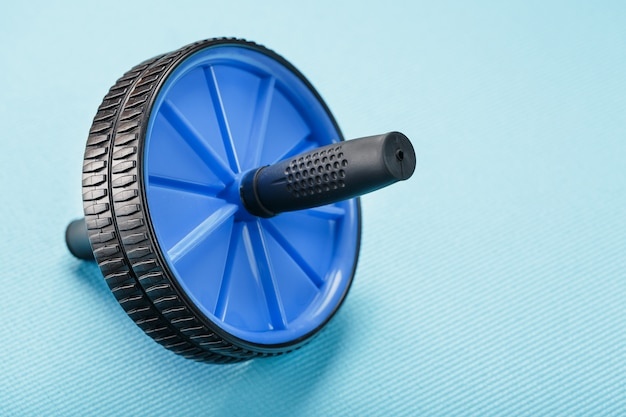 Blue roller for abs pumping classes on a blue fitness mat.