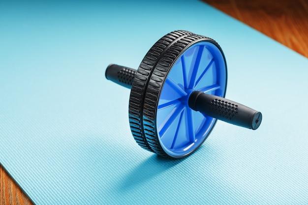 Синий ролик для занятий накачкой пресса на синем фитнес-мат.