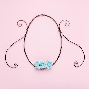 ピンクの背景の楕円形の空のフレームに青いバラ