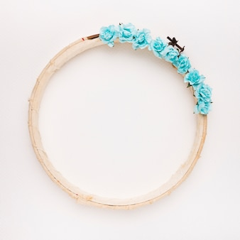 Blue roses on the wooden circular border frame on white backdrop