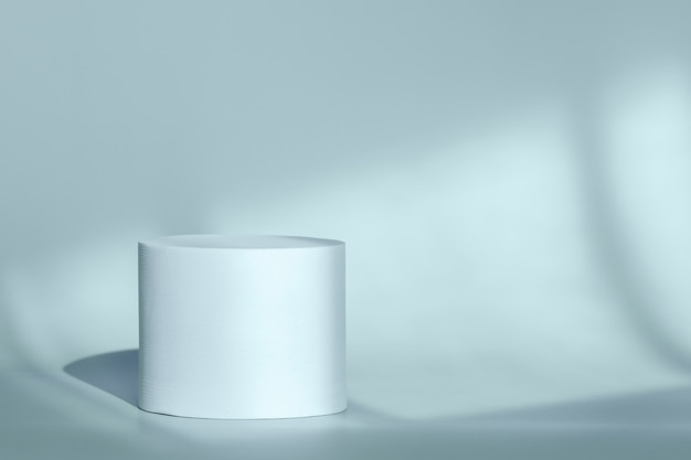 Blue round pedestal podium for packaging presentation on backdrop with room shadows from window