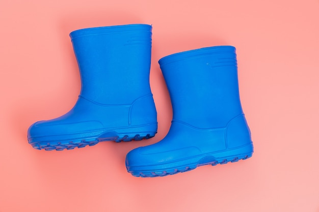 Blue rubber boots on a pink background. shoes for rainy weather and puddles. shoe store. protect your feet from dampness and dirt.