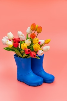 Blue rubber boots with multicolored tulips on a pink background. shoes for rainy weather and puddles. shoe store. protect your feet from dampness and dirt.