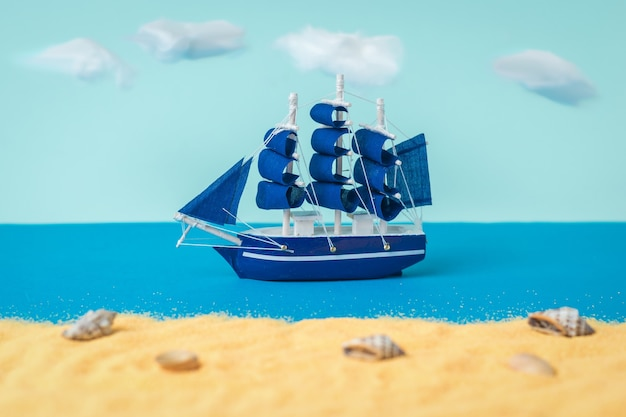 A blue sailboat sailing past a sandy beach. the concept of travel and adventure.
