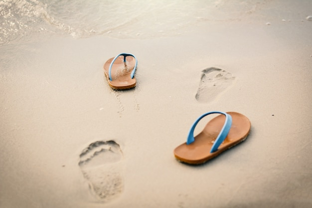 Blue sandal with footprint on the beach concept time to travel