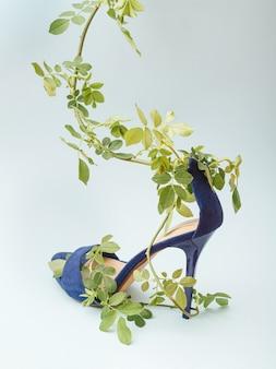 파란색 배경에 장미 꽃잎으로 싸인 파란색 샌들 하이힐 신발. 자연과 아름다움 개념입니다.