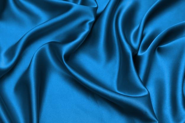 Blue satin, silky fabric, wave, draperies. beautiful textile backdrop.