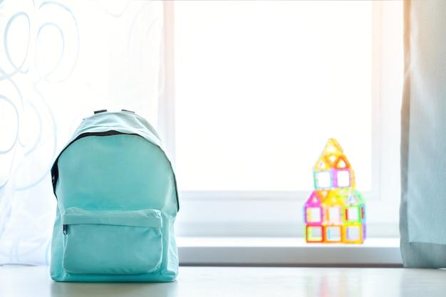 晴れた日の子供部屋のインテリアの上のテーブルの上の青い学校のバックパック