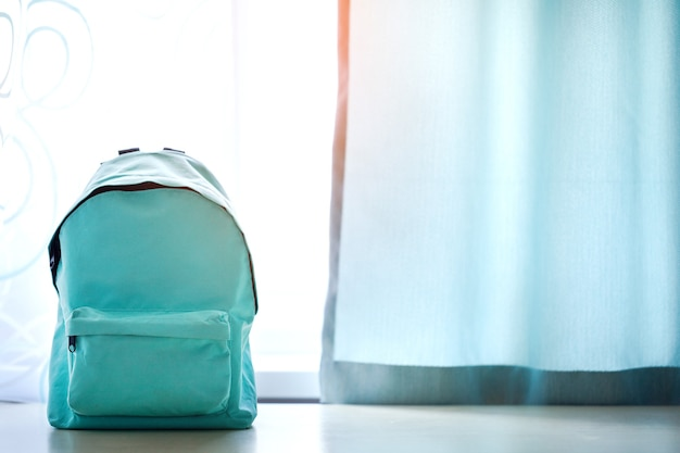 Blue school backpack on table over children room interior in sunny day