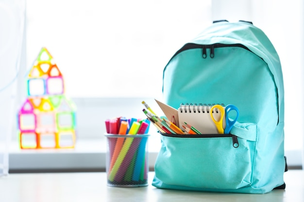 Blue school backpack with school supplies on table in children room across from the window in sunny day