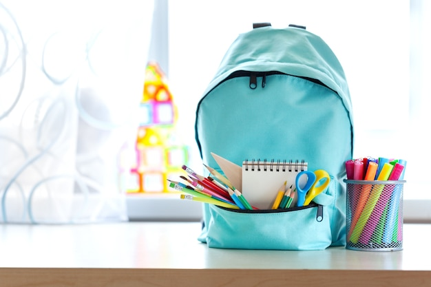 Blue school backpack with school supplies on table over children room interior in sunny day
