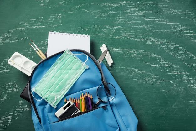 Синий школьный рюкзак на зеленой доске с защитной маской и канцелярскими принадлежностями