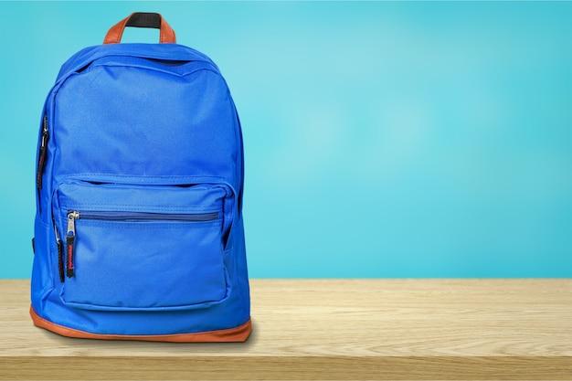 Синяя школьная сумка на фоне