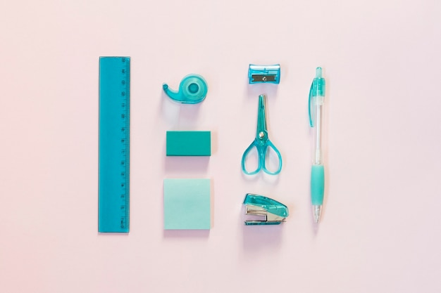 Blue school supplies on light pink background
