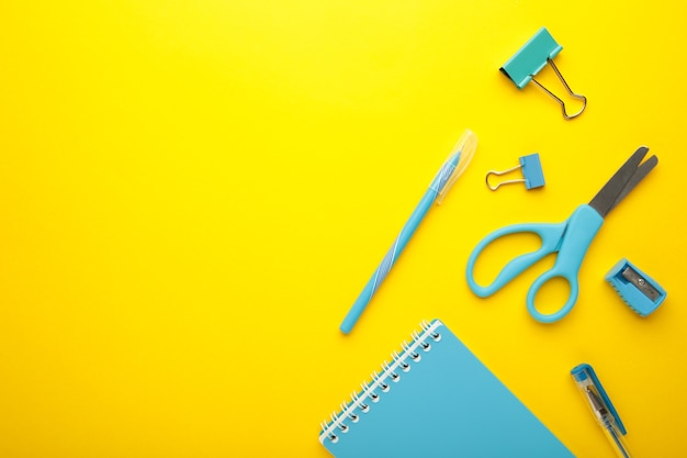 Blue school supplies on yellow background. back to school concept. top view.