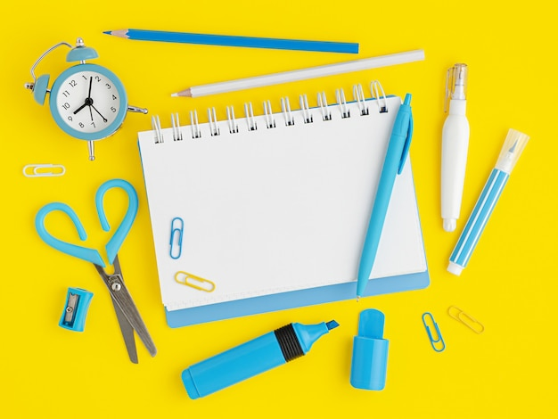 Blue school supplies on yellow background with empty notebook blank. overhead
