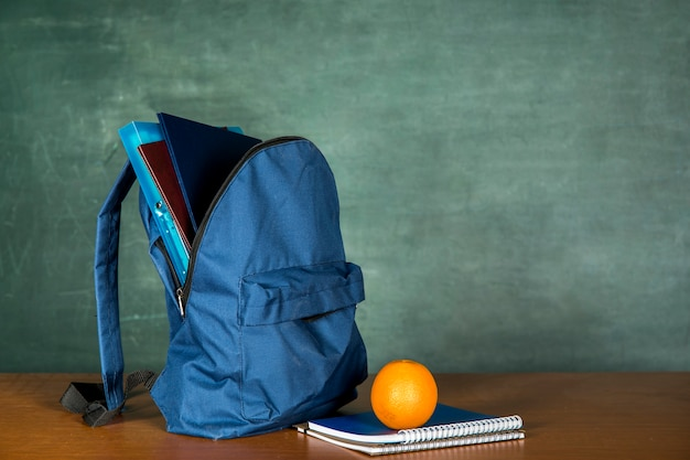 Blue schoolbag with copybook and orange