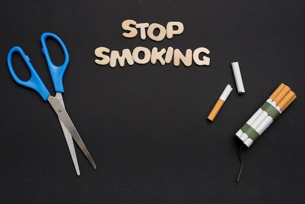 Blue scissor with stop smoking text and cigarette on black backdrop