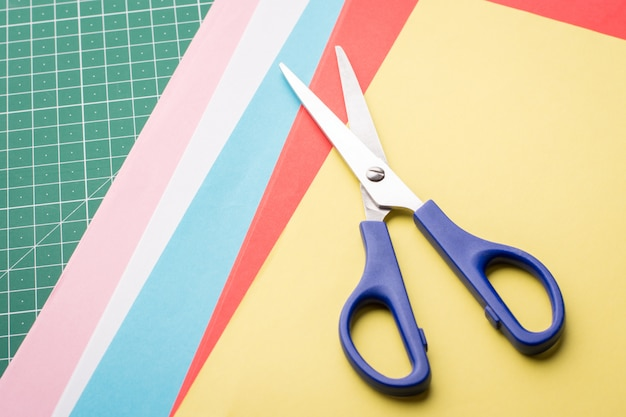 Blue scissors on papers of different colour for making origami