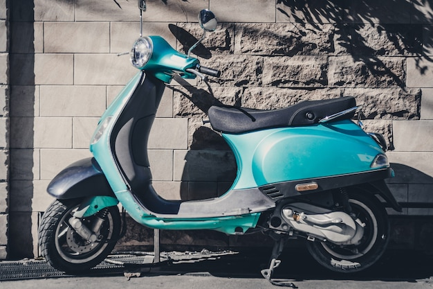 Blue scooter stands against the background of a stone wall