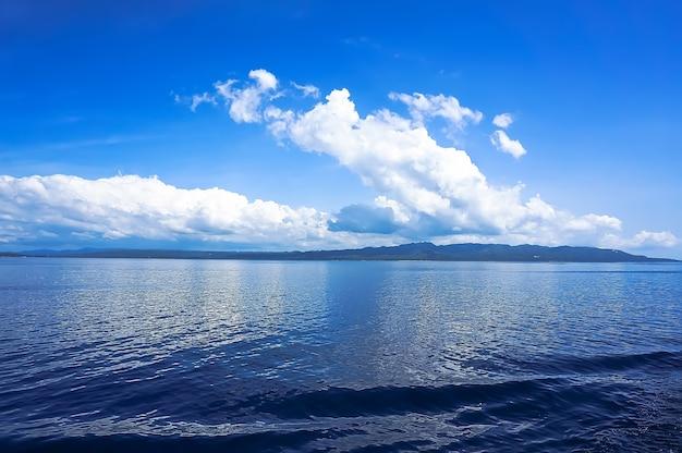 白い積雲と青い海、青い空の地平線