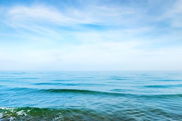Голубая морская вода с волнами и белыми облаками на небе. спокойный тропический пейзаж