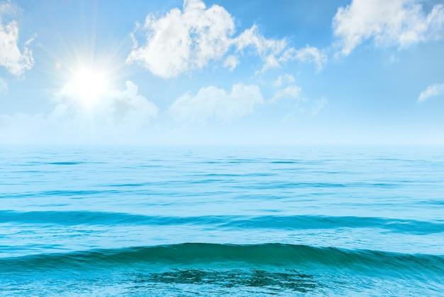 Голубая морская вода с волнами, солнцем и белыми облаками на небе. спокойный тропический пейзаж