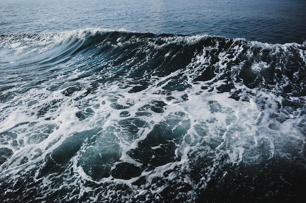 배경에 흰색 파도와 푸른 바다 물입니다.