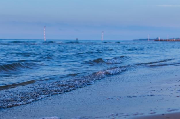Blue sea waves on the evening sandy beach.