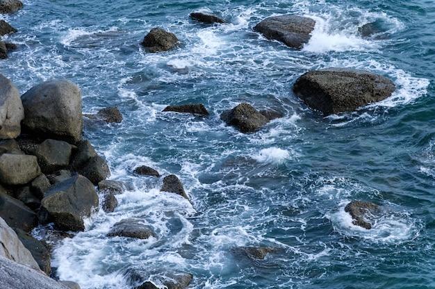 海岸線の岩に波が当たる青い海