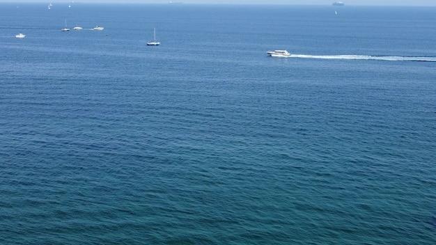 青い海、ヨット、ボート、船が水に浮かんでいます。港の近くのドローンの航空写真。
