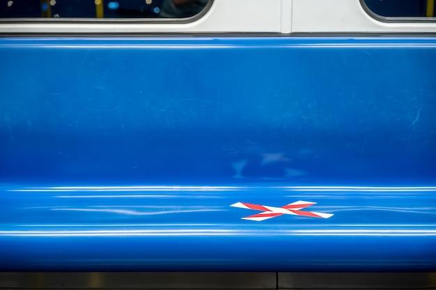 코로나바이러스(covid-19) 기간에 교차 표시 테이프가 있는 기차의 파란색 좌석 열. 교통수단에서의 사회적 거리두기를 의미합니다.