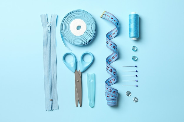 Синие швейные принадлежности на синем фоне, вид сверху