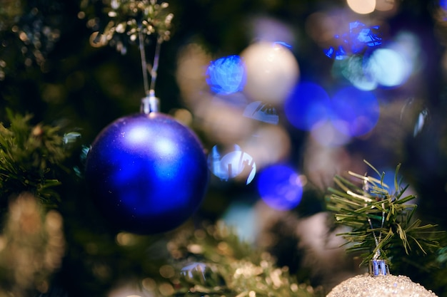クリスマスツリーの青い光沢のあるボール冬祭りの雰囲気の休日の装飾とボケライトne ...