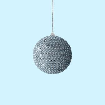 パステルブルーの背景に青い光沢のあるクリスマス安物の宝石の装飾
