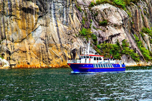 The blue ship on background of majestic cliffs