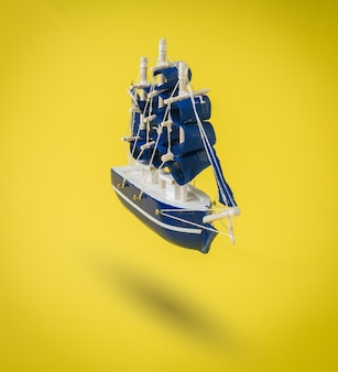 A blue ship with sails on a bright yellow surface. a dream come true.