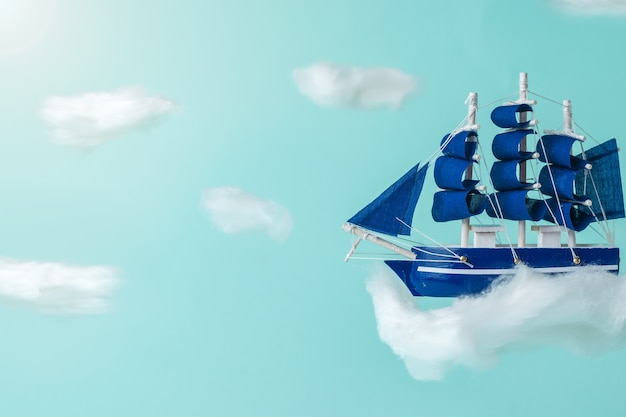 A blue ship with sails flying in the clouds. a dream come true.