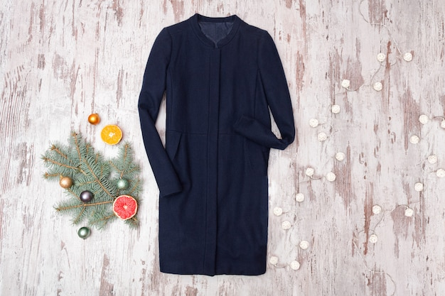 Blue shirt, decorated fir branch and garland on wooden background. fashionable concept.