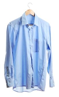 白で隔離される木製ハンガーに青いシャツ