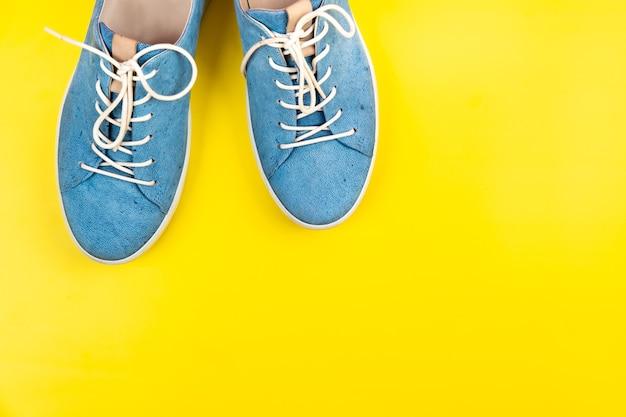 파란색 신발은 격리된 노란색 배경에 서 있습니다.