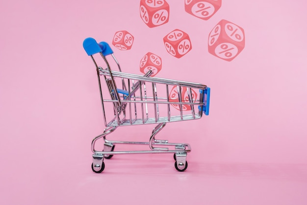 Blue shopping cart with red percentage signs on cubes on pink background, retail and discount concept