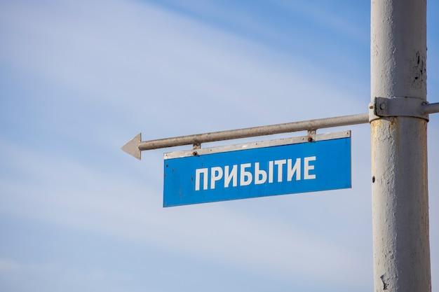 交通機関の到着の碑文と青い看板。ロシア語で。高品質の写真