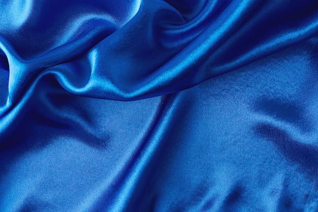 ひだに青い絹の背景。波状のサテンの表面の抽象的なテクスチャ